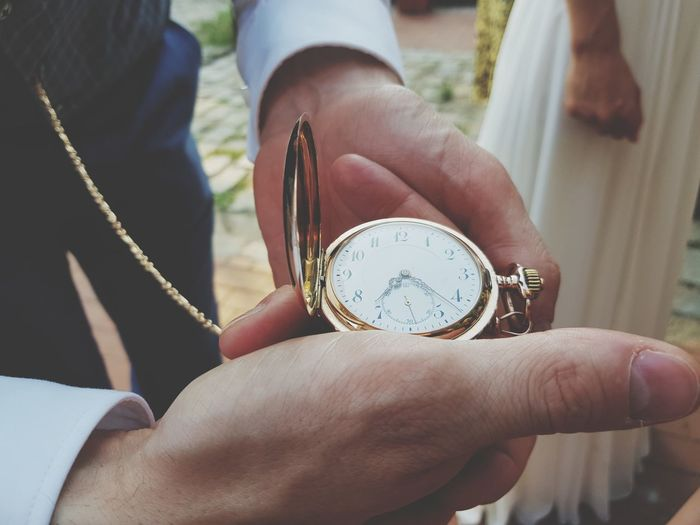 Midsection of man holding pocket watch