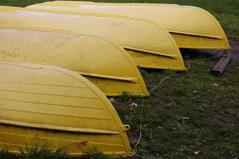Four yellow boats. Boats Canoeing Yellow Lined Up Upside Down On Land Four Outdoors Outdoor Recreation
