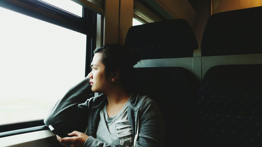 Thoughtful Woman Looking Away While Traveling In Train