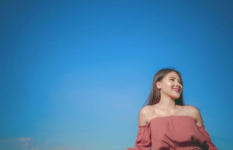 Smiling young woman against blue sky