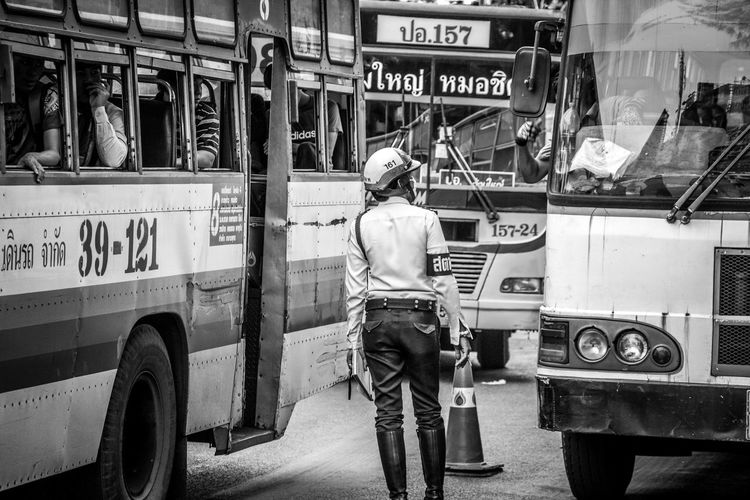 Traffic cop standing on street with buses in traffic jam