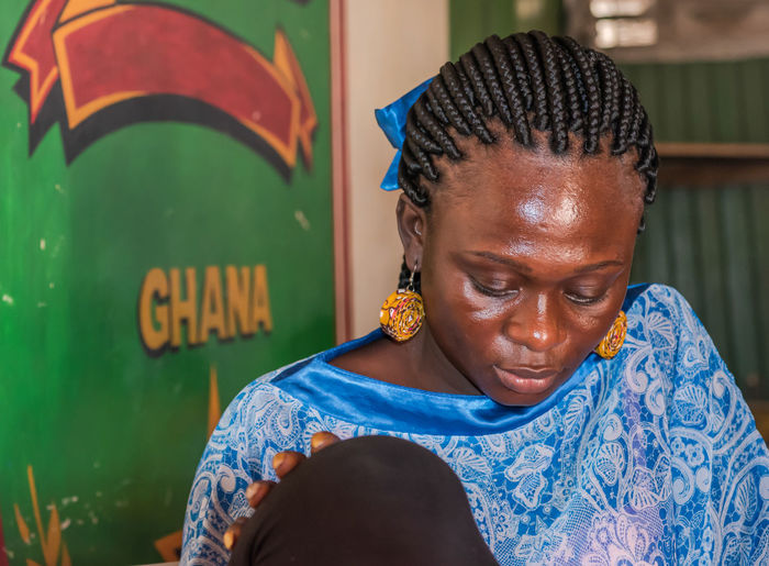 Africa ghana woman sitting inside a bar and having all the attention on her mobile phone