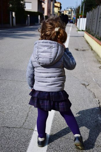 Rear View Of Girl Standing On Street During Sunny Day