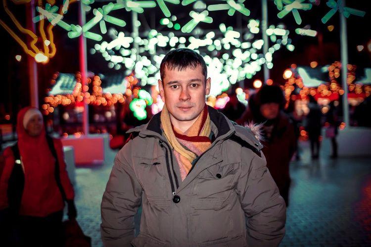 Portrait of man in illuminated christmas tree in winter