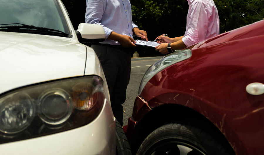 Midsection Of Men Doing Paperwork While Standing By Cars