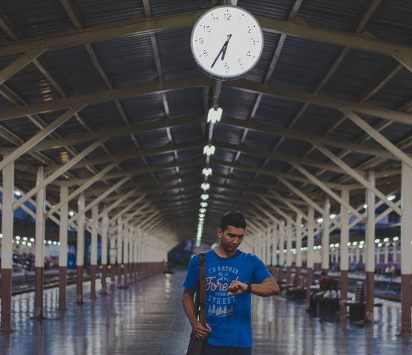 Working Architecture Built Structure Casual Clothing Ceiling Clock Front View Illuminated Indoors  Instrument Of Time Leisure Activity Lifestyles Men One Person Railroad Station Real People Standing Three Quarter Length Time Transportation Waiting Young Adult
