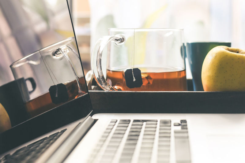 Close-up of laptop on table with coffee and apple