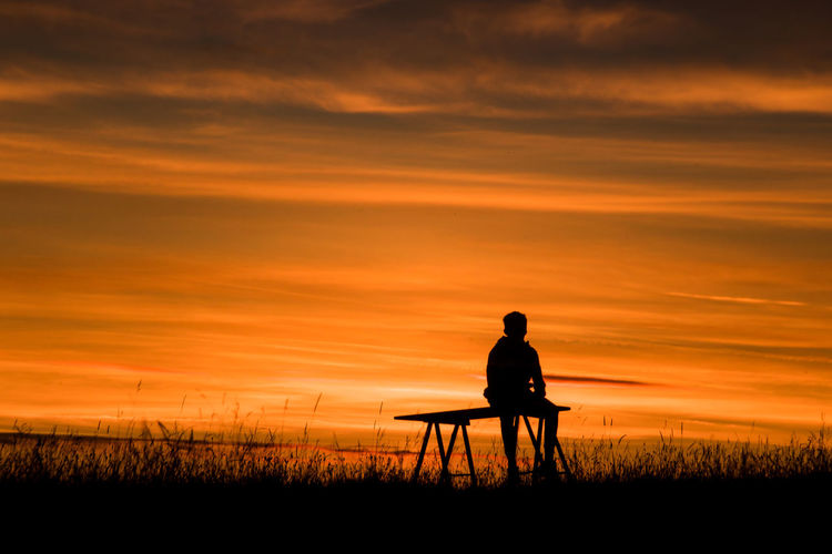 Silhouette man sitting on field against sky during sunset