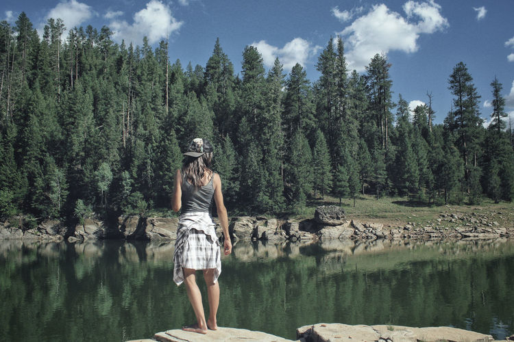A woman in a hat stands on the edge of a mountain lake Athletic Camping Exploring Green Hat Hiking Lifestyle Standing Trees Woman Adventure Blue Sky Brunette Clouds Forest Lake Looking Mountain Mountains Outdoors Outside Reservoir Sky Summer Water