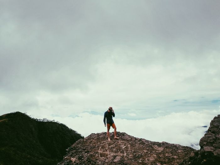 View Of Man Standing On Rock Against Sky