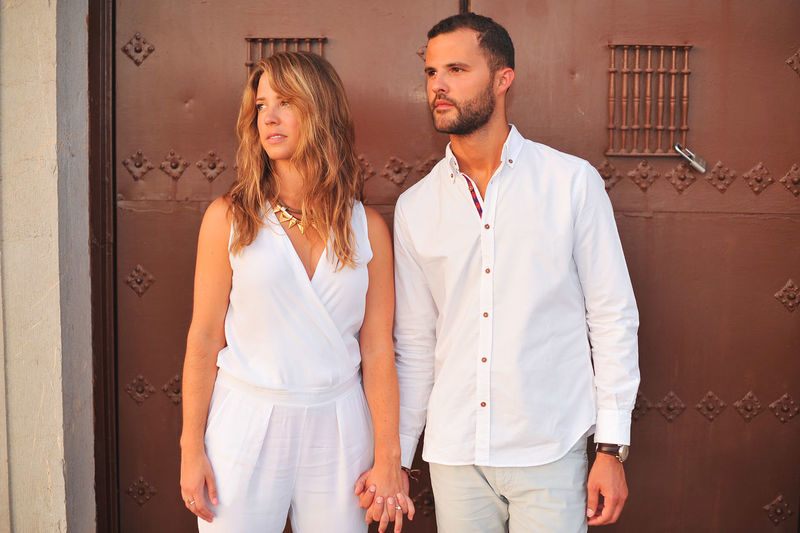 Young couple looking away while holding hands against door in city
