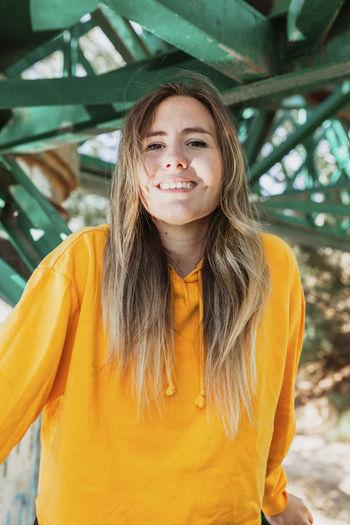 Portrait of young woman sitting on railway bridge