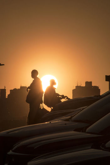 Silhouette of man in city against sky during sunset