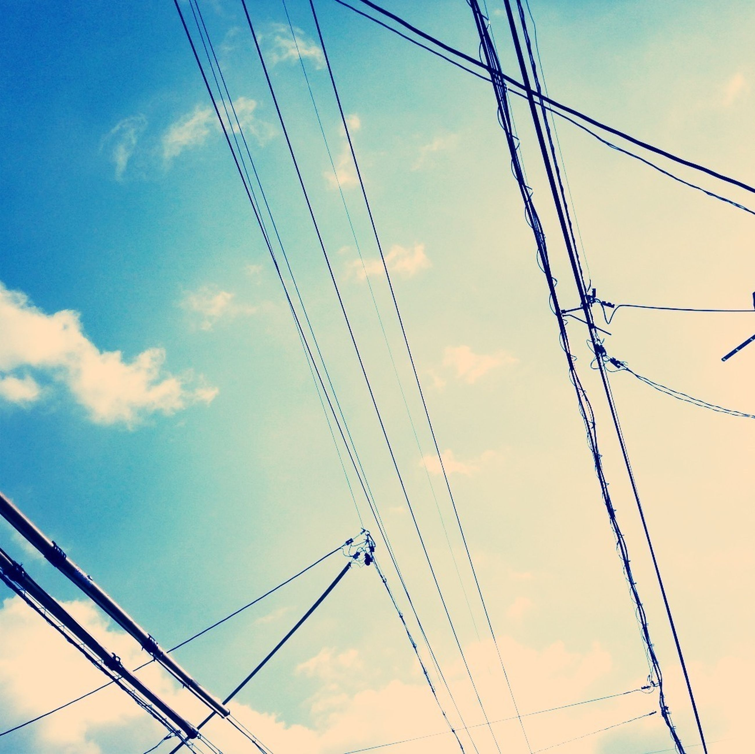 power line, cable, power supply, electricity pylon, low angle view, electricity, connection, sky, fuel and power generation, technology, cloud - sky, power cable, cloud, blue, complexity, outdoors, no people, cloudy, day, telephone pole