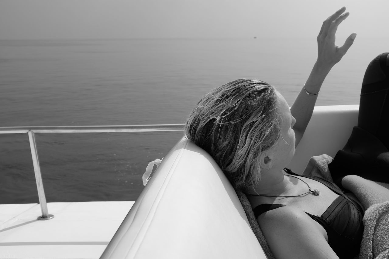 Woman resting on boat while sailing in sea