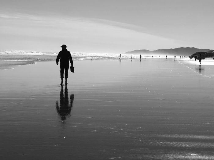 Rear view of silhouette man walking on beach against sky