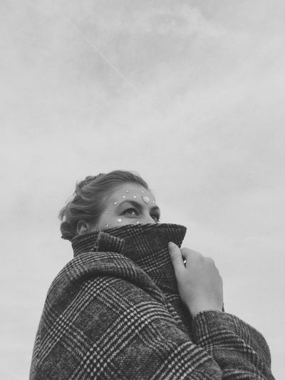 Low angle portrait of woman standing against sky during winter