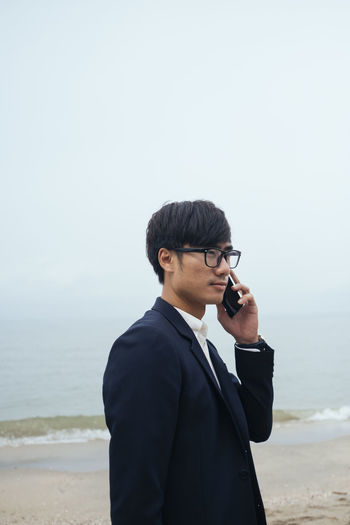 Young man using mobile phone at beach against sky