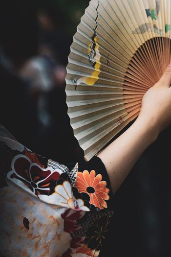 Midsection of woman holding hand fan