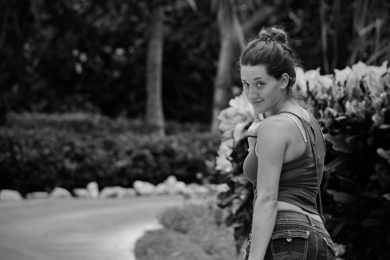 Portrait of young woman standing by plants in park