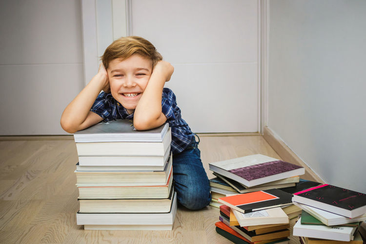 Indoors  Males  Childhood Child Children Only Kid Boys Caucasian Indoors  Home Interior Learning Studying Elementary Age Innocence Blond Hair Cute One Person People Book Publication Stack Education Emotion Happiness Student Literature School Supplies Back To School Smiling Floor Portrait