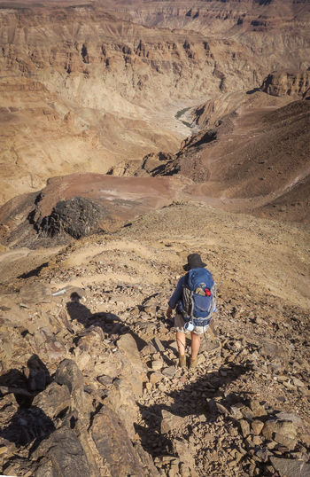 Female hiker walking downhill towards arid desert canyon Adventure Backpack Bag Beauty In Nature Exploration Explore Fitness Hike Hiker Hiking Hiking Mountain Mountain Range Nature Nature One Person Outdoor Outdoor Photography Outdoors Rugged Scenics Summer Travel Wild Wilderness