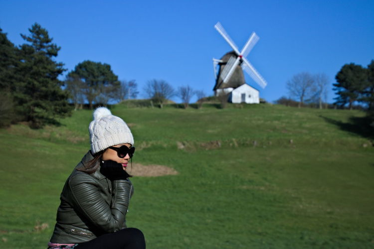 Side view of young woman in warm clothing sitting on grassy field against clear sky with traditional windmill in background