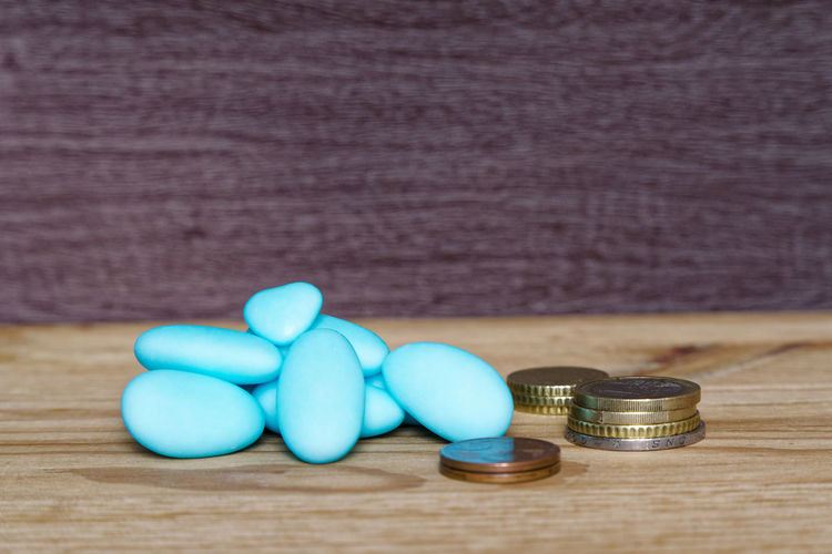 Close-up of blue medicines and coins on wooden table