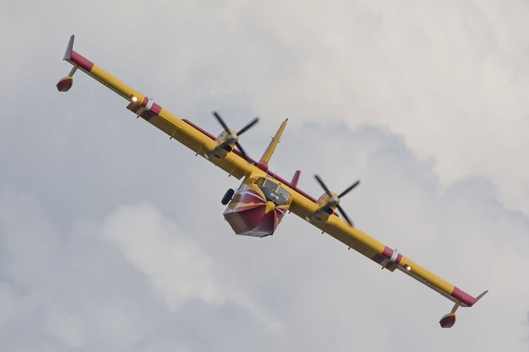 Low angle view of canadair plane flying against cloudy sky