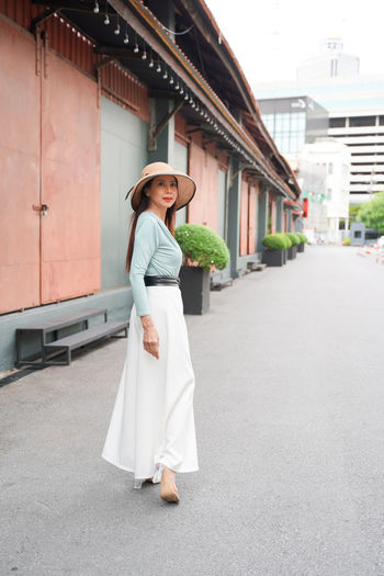 Full length of woman standing by building in city