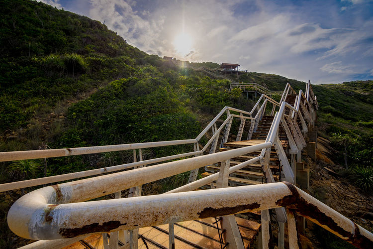 Concrete and steel stairs in a dangerous condition of disrepair lead up a hillside towards shelters and the setting sun. Perhentian island, Malaysia. Stairs Architecture Beauty In Nature Built Structure Cloud - Sky Concrete Day Land Mountain Nature No People Outdoors Plant Railing Scenics - Nature Sky Staircase Sunlight Sunset Tranquil Scene Tranquility Tree Wood - Material