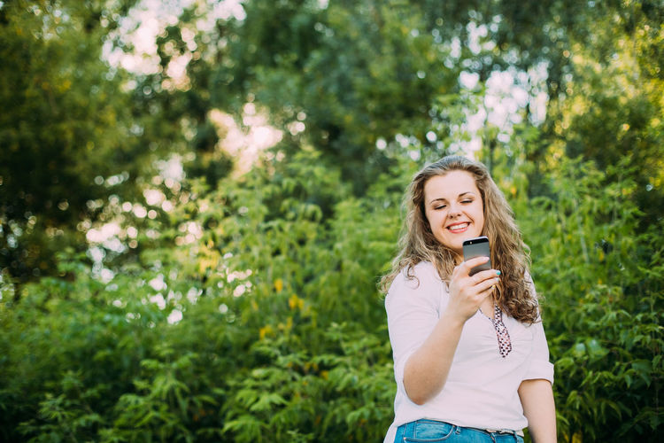 Cheerful Young Woman Using Phone Against Plants