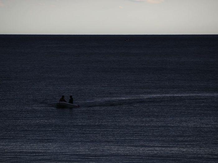 Silhouette people in sea against sky
