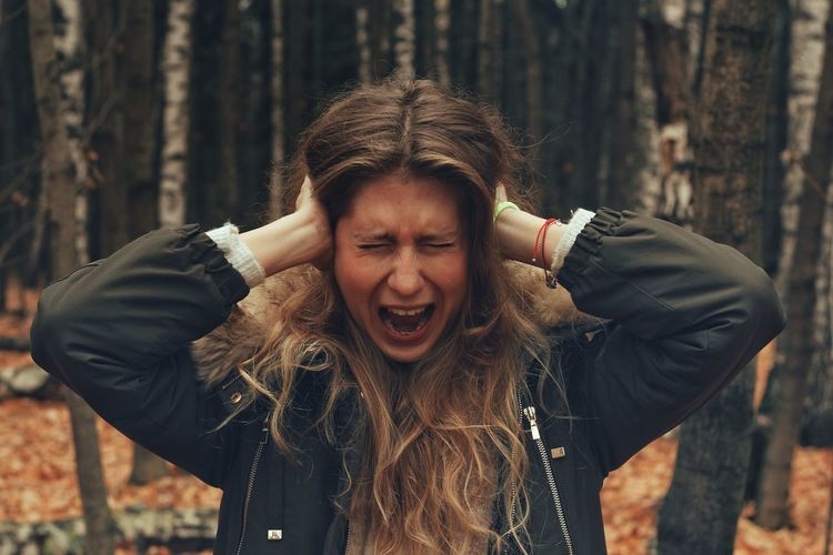 Young woman screaming while covering ears in forest