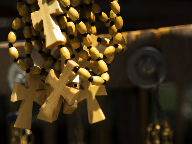 Wooden handmade crosses at the fair during the holiday Cross Faith Holiday Spirituality Belive Celebration Close-up Day Fair Focus On Foreground Gold Colored Handmade Illuminated Indoors  Large Group Of Objects No People Religion Wooden Yellow