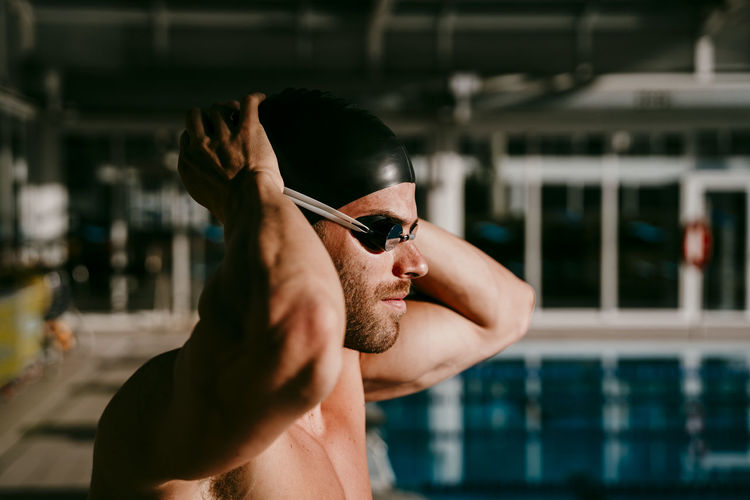Portrait of young man wearing sunglasses at swimming pool