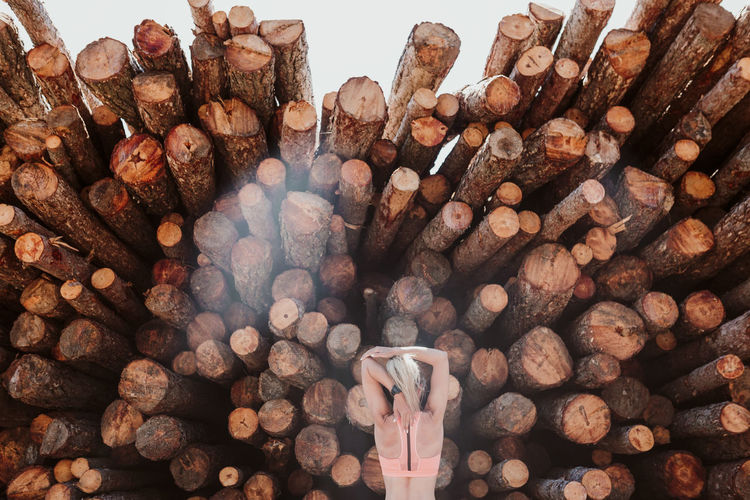 Woman against stack of logs
