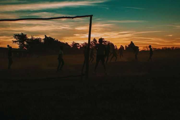 Silhouette people on field against sky during sunset