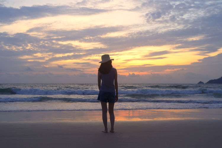 Full length rear view of woman standing at beach against sky during sunset