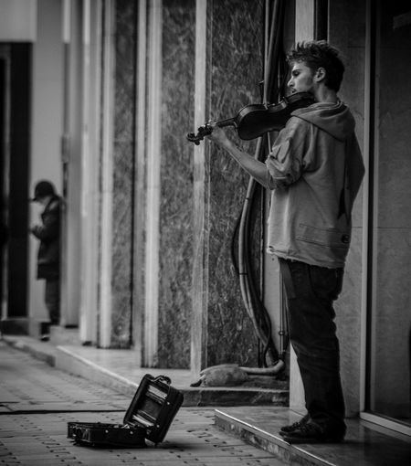 Homeless Man Playing Violin At Street