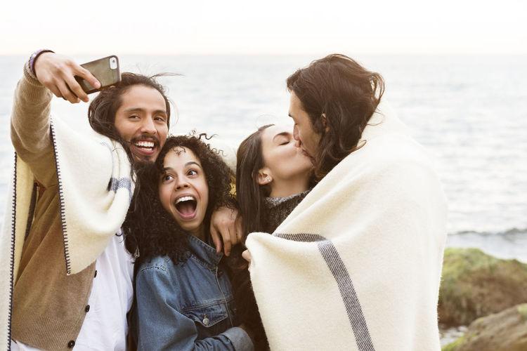 Friends clicking selfie at beach against sea