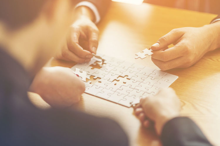 Midsection Of Business People Playing With Jigsaw Puzzle On Table