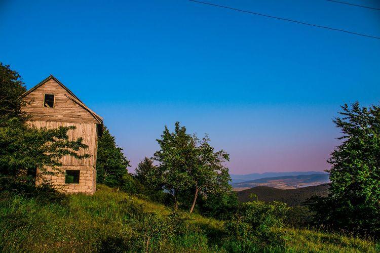 House on field against clear blue sky