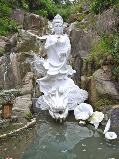 Kwun Yam Statue sits in front of a waterfall alongside the monastery's upper level. Day Kwun Yam Monastery No People Outdoors Statue Temple Ten Thousand Buddhas Water