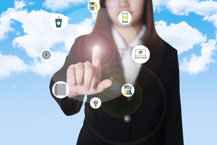 Midsection of businesswoman touching icons on digital display against blue sky