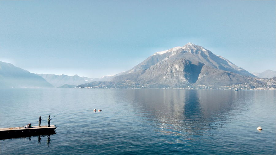 Fishermen Fisherman Tranquility Tranquil Scene Lago Di Como Bird Water Mountain Snow Lake Snowcapped Mountain Blue Clear Sky Sky Mountain Range