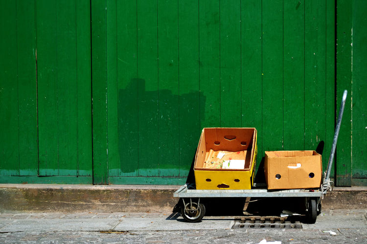 Empty boxes on push cart against wooden wall during sunny day