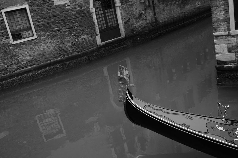 Boat moored on canal by building