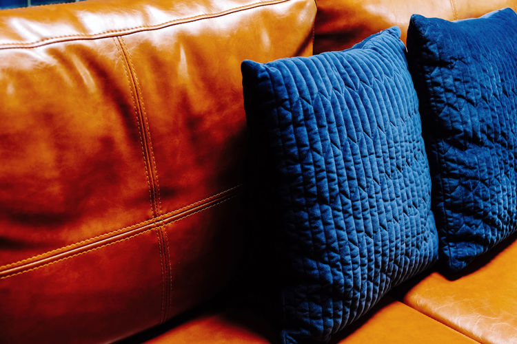 Close up detail of blue pillow on leather sofa Decor Interior Decorating Pillow Black Color Blue Brown Close-up Clothing Comfortable Cushions  Decoration Fashion Furniture Home Interior Indoors  Jeans Leather Leather Sofa No People Orange Color Pattern Pillow Relaxation Seat Sofa Still Life Stuffed Textile