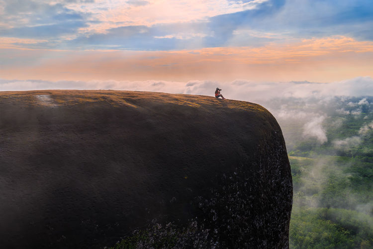 Woman sitting sunrise watching on the three whale rock mountain at Bueng Kan Province,Thailand Bueng Kan Family Rock Adventure Beauty In Nature Cliff Cliffside Cloud - Sky Clouds And Sky Colorful Fog Landscape Mist Outdoor Paradise People Rocky Mountains Sky Summer Sun Sunrise Wallpaper Women